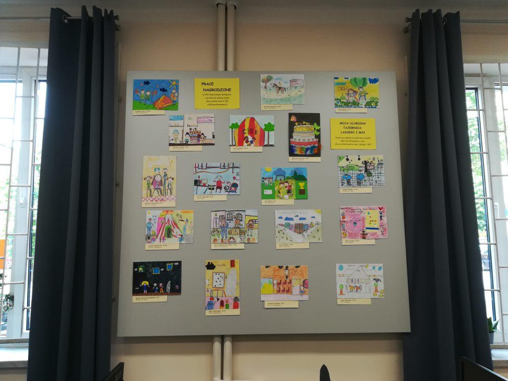 Tablica zawieszona między oknami a na niej kolorowe obrazki - nagrodzone prace konkursowe.
