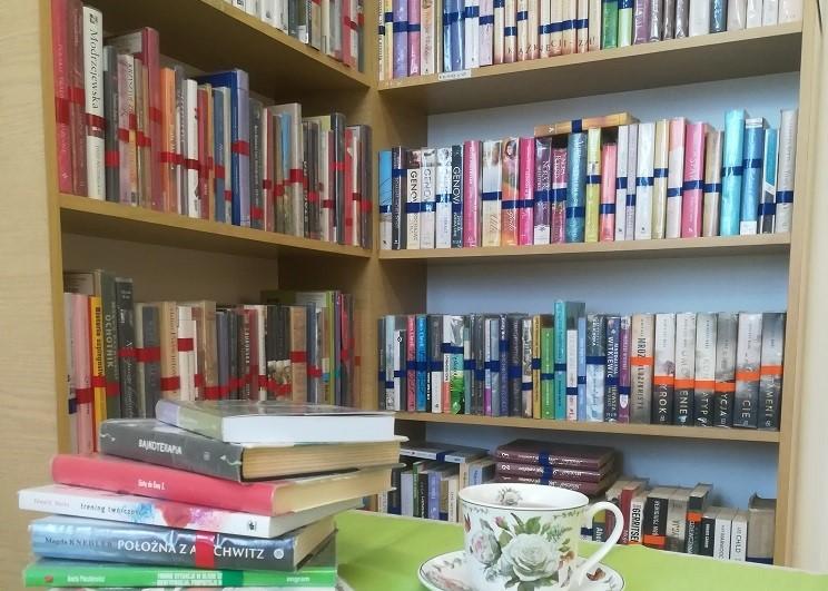 Filiżanka i stos książek po lewej stronie, w tle regały z kolorowymi ksiażkami.